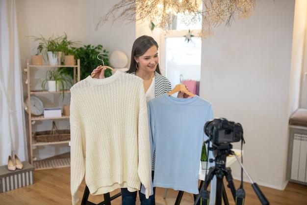 Bella giovane donna in piedi davanti alla telecamera mentre dà consigli sui vestiti