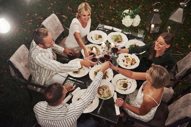 Buona fortuna per tutto. vista dall'alto. un gruppo di amici in abiti eleganti ha una cena di lusso