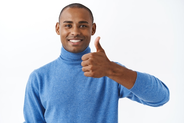 Buona fortuna, bel lavoro. il ritratto del primo piano dell'uomo afroamericano soddisfatto e bello mostra il pollice in su come, l'approvazione o raccomanda il segno