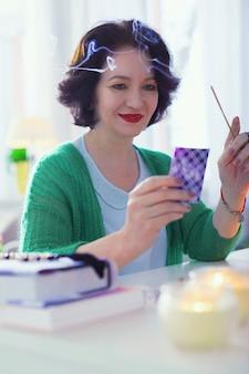 Buon significato. bella donna positiva che sorride mentre esamina la carta dei tarocchi
