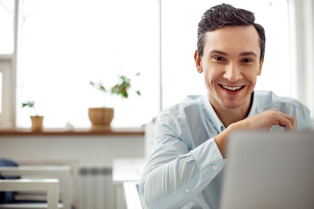Buon umore. uomo dai capelli scuri dagli occhi scuri allerta attraente che sorride e lavora al suo laptop mentre era seduto al tavolo
