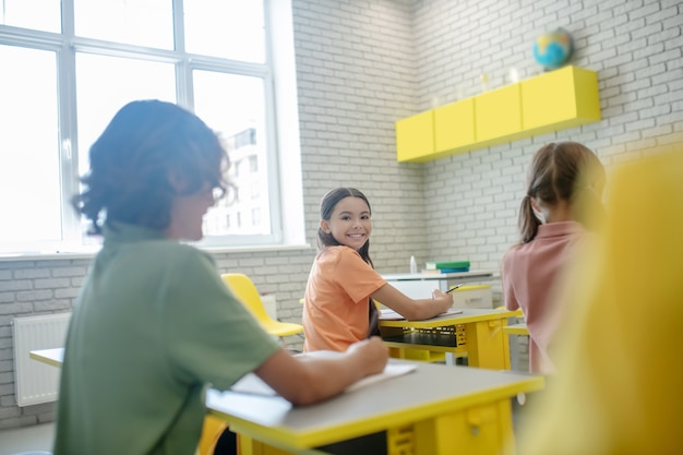 Buon umore. ragazza dai capelli scuri seduto alla scrivania in classe e sorridente al suo compagno di classe