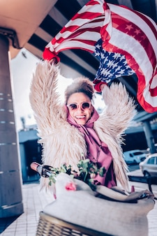 Buon umore. piacevole ragazza internazionale che mantiene il sorriso sul viso mentre mostra la bandiera americana