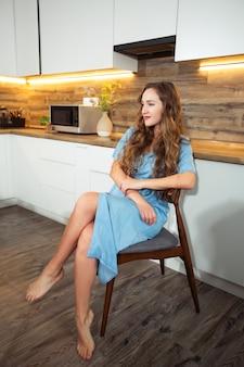 Buongiorno . la giovane donna attraente sta riposando a casa. ragazza in cucina. il modello alla moda della giovane donna sexy in un vestito blu alla moda dai jeans dell'annata si siede sulla sedia della cucina nella stanza del cuoco.