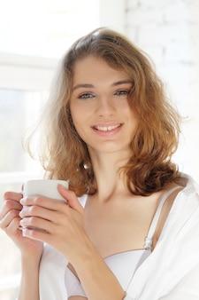 Buongiorno! bella donna che indossa lingerie bianca che beve caffè al mattino seduto vicino alla finestra.