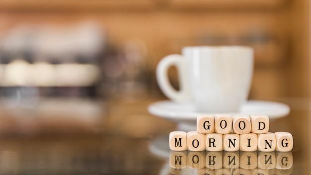 Buongiorno blocchi cubici con la riflessione della tazza di caffè sul vetro