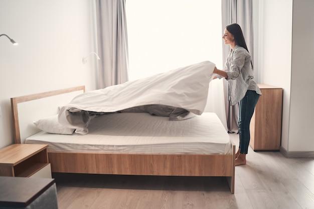 Buongiorno. felice ragazza bruna che esprime positività mentre si trova in posizione semi vicino al suo letto