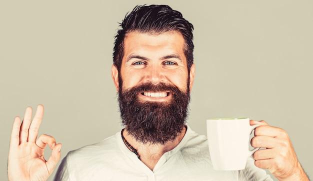 Buongiorno, uomo tè, ok. uomo sorridente dei pantaloni a vita bassa con la tazza di caffè fresco, uomo felice che mostra il segno giusto. concetto di mattina.