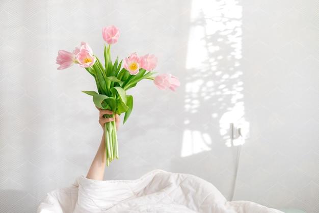 Buongiorno tulipani rosa nella mano di una donna a letto, auguri di compleanno, giornata internazionale della donna, san valentino, regalo, fiori, bouquet rosa, tulipani primaverili, sorpresa