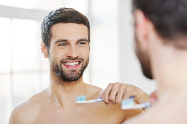 Buon giorno. vista posteriore di un bel giovane uomo con la barba che tiene lo spazzolino da denti e sorride mentre sta in piedi contro uno specchio