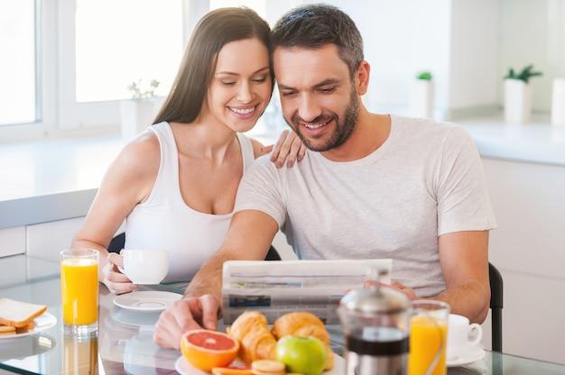 Il buongiorno inizia da una buona notizia. bella giovane coppia che si lega e legge il giornale insieme mentre è seduta in cucina e fa colazione