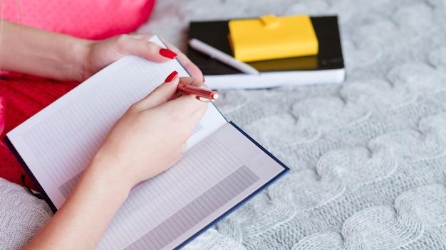 Buongiorno con il diario. il letto è l'ufficio. donna che pianifica e prende appunti.