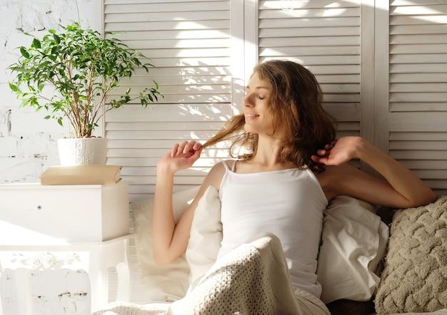 Buongiorno! giovane bella donna che si sveglia nel suo letto completamente riposato. uno stile di vita sano. dolce casa.