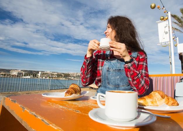 Buongiorno. giovane donna con una colazione francese con caffè e croissant seduti all'aperto sulla terrazza del caffè in riva al mare.