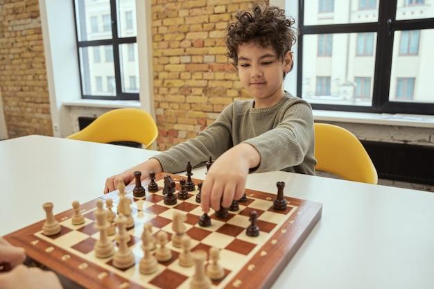 Buona mossa ragazzino attento che fa una mossa mentre è seduto in classe e gioca a scacchi