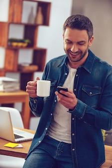 Buone notizie dal collega. bel giovane che tiene una tazza di caffè e guarda il suo smartphone con un sorriso mentre si trova vicino al suo posto di lavoro in ufficio in