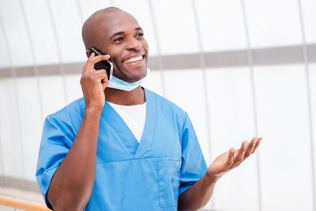 Buone notizie! felice giovane medico africano in uniforme blu parlando al telefono cellulare e gesticolando