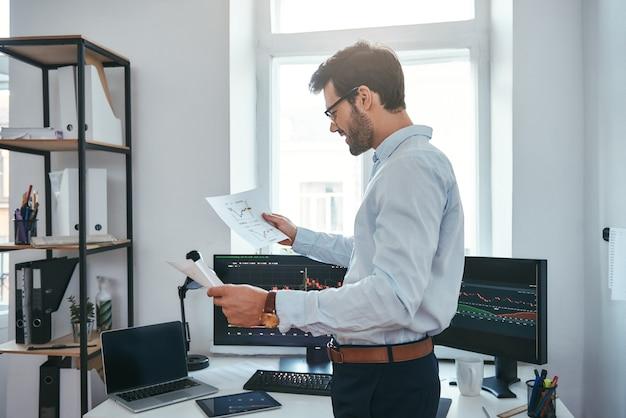 Buone notizie felice giovane uomo d'affari o commerciante in occhiali e abbigliamento formale guardando il commercio