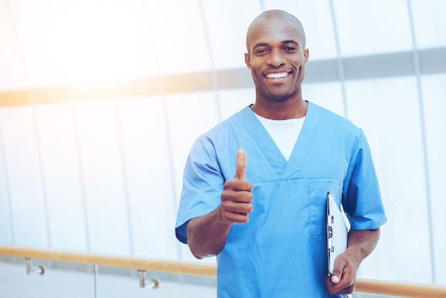 Buone notizie per te! felice giovane medico africano in uniforme blu che tiene appunti e mostra il pollice in su