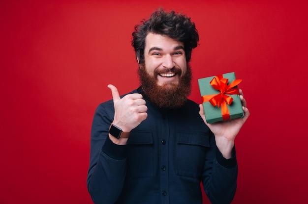 Buon regalo. qualcuno che si gode le vacanze, un ragazzo barbuto che tiene in mano una scatola regalo e mostra il pollice in alto su sfondo rosso