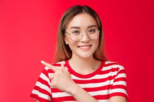 Buona opportunità dietro l'angolo carina ragazza asiatica con gli occhiali maglietta estiva a righe che punta a sinistra...