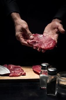 Buona ricezione. chiuda in su delle mani di chef tenendo la carne durante la cottura e il lavoro in ristorante.