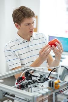 Buon risultato. affascinante giovane ingegnere che scruta il pomodoro rosso stampato in 3d, dopo averlo creato con una stampante 3d
