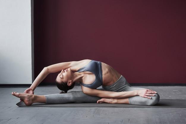 In salute. la ragazza con un buon tipo di corpo fitness ha esercizi nella stanza spaziosa