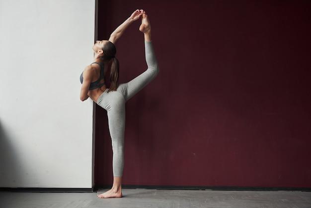 Buon allungamento. la ragazza con un buon tipo di corpo fitness ha esercizi nella stanza spaziosa