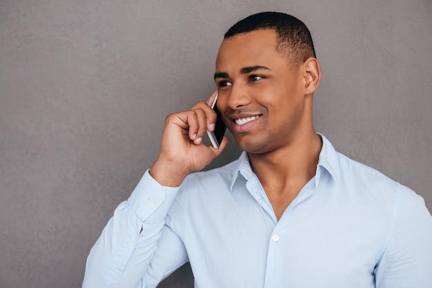 Ben detto. fiducioso giovane africano parlando al telefono cellulare e sorridente