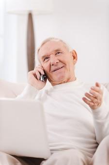Ben detto. felice uomo anziano che parla al telefono cellulare e tiene il laptop sulle ginocchia mentre è seduto su una sedia nel suo appartamento