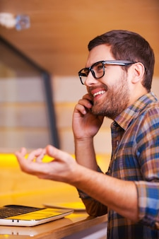 Buona chiacchierata con l'amico. bel giovane che parla al telefono cellulare e sorride mentre è seduto al bar