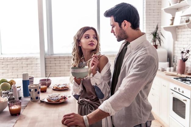 Buon tempo. giovane donna dai capelli lunghi che indossa una camicia bianca e il suo attraente marito gustando la colazione