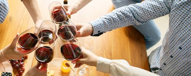 Buone sensazioni. mani di amici, colleghi mentre bevono birra, si divertono, tintinnano bottiglie, bicchieri insieme.