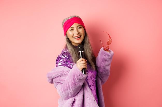 Splendida donna anziana asiatica che canta al karaoke nel microfono, esegue una canzone e sembra felice, in piedi su uno sfondo rosa.
