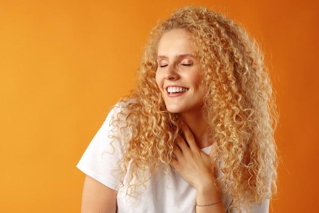 Splendida bella giovane donna con i capelli ricci che propone alla macchina fotografica