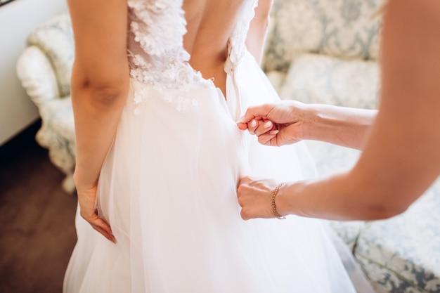 La sposa splendida e bionda in vestito di lusso bianco si sta preparando per il matrimonio. i preparativi del mattino. donna che indossa il vestito.