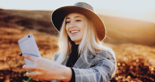 Splendida signora caucasica bionda con un bel cappello che fa un selfie mentre sorride un campo soleggiato
