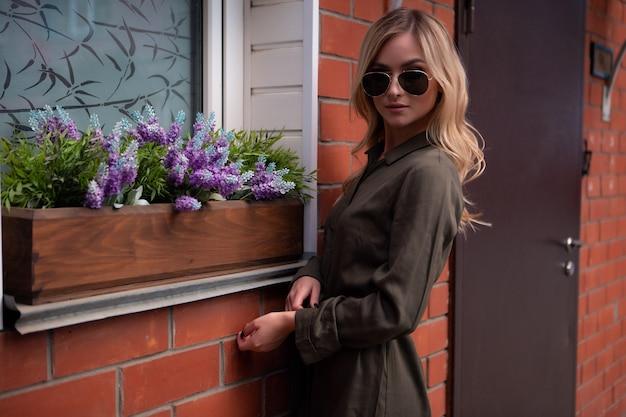 Splendida bionda in occhiali alla moda si aggiusta i capelli alla finestra di una casa decorata con fiori dalla strada.