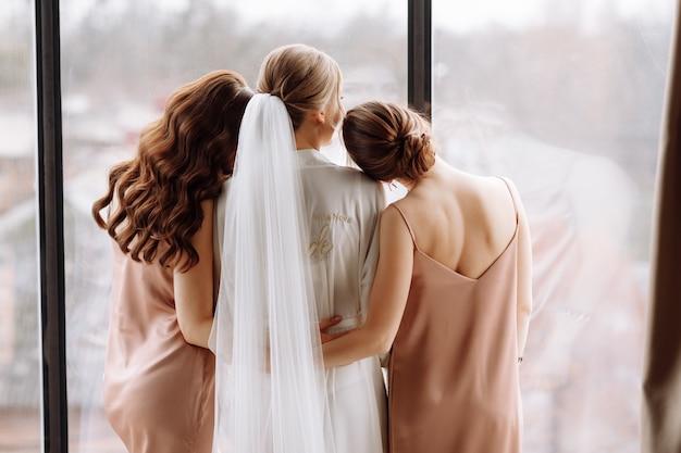 La splendida sposa con le migliori damigelle si sta divertendo nella camera d'albergo vicino alla grande finestra.