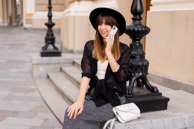 Splendida donna bruneete in elegante abito autunnale e cappello posteriore che parla al telefono cellulare per strada nella vecchia città europea