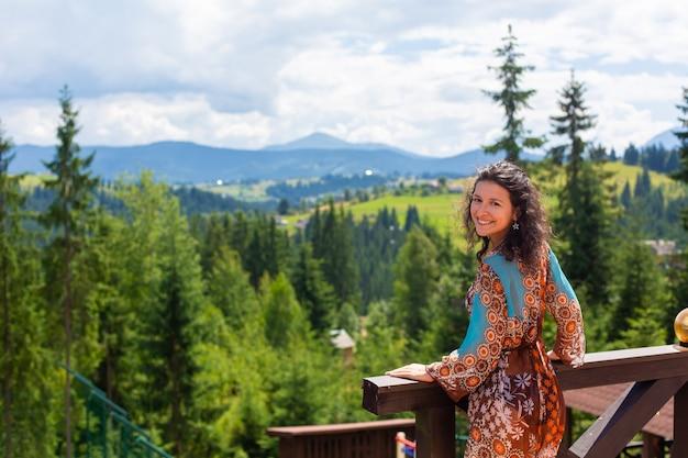 Una splendida ragazza bruna gode della bellezza della natura in piedi sulla terrazza con vista mozzafiato sul paesaggio montano.