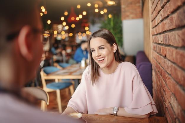 Seduta castana splendida nel ristorante con il suo ragazzo e bere caffè