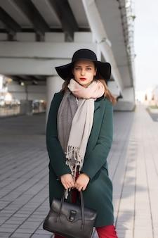 Splendida donna bruna in cappotto verde e cappello nero in posa in città