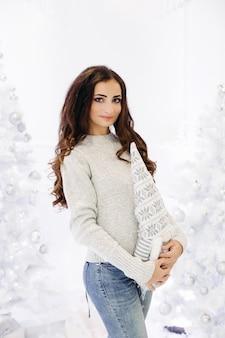 Splendida donna castana con trucco perfetto e pelle liscia che indossa un maglione grigio in posa in studio decorato per le vacanze di capodanno