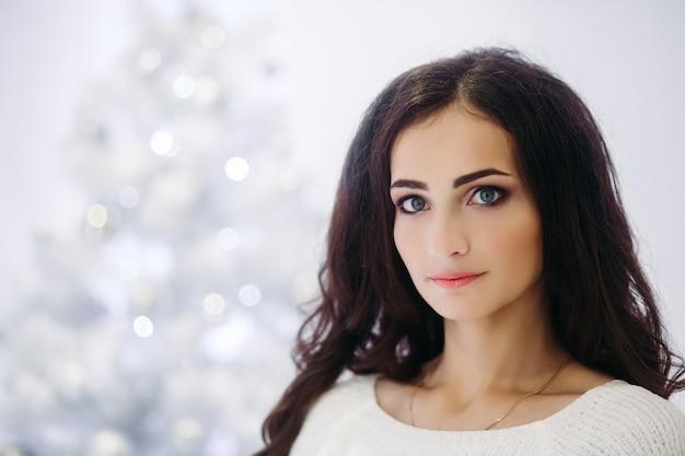 Splendida donna castana con trucco perfetto e pelle liscia che indossa un maglione grigio in posa