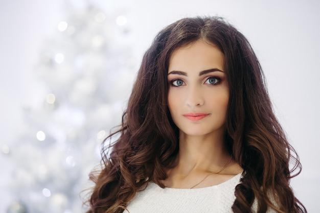 Splendida donna bruna con trucco perfetto e pelle liscia che indossa un maglione grigio