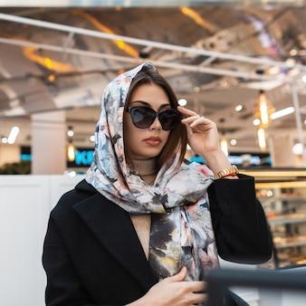 La giovane bella donna di affari splendidi con la sciarpa di seta dell'annata sulla testa in occhiali da sole sta riposando in caffè. modello di moda ragazza elegante alla moda che si siede nel centro commerciale. signora alla moda attraente.