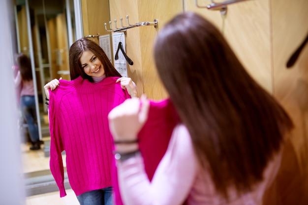 Una splendida ragazza allegra che sta per provare il nuovo maglione rosa che le piace molto nel cambiare armadio in negozio.