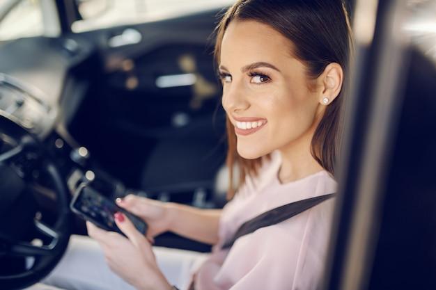 Giovane seduta castana caucasica allegra splendida in automobile con la cintura di sicurezza sopra e messaggio di battitura a macchina.